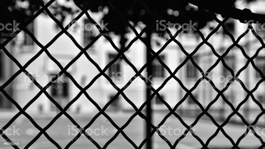 Black and white building behind fence stock photo
