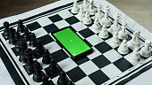 istock Black and white chess pieces and a smart green screen phone in the middle. Chess application concept 1237382689