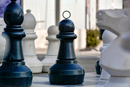 Chess pieces on board in large scale outdoor chessboard. Pawn, bishop and knight fight for winning tournament