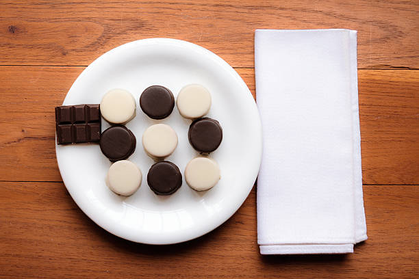 Black and white chocolate alfajores on white plate - foto de stock