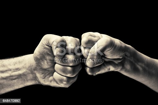 istock black and white clash of two fists 648470992