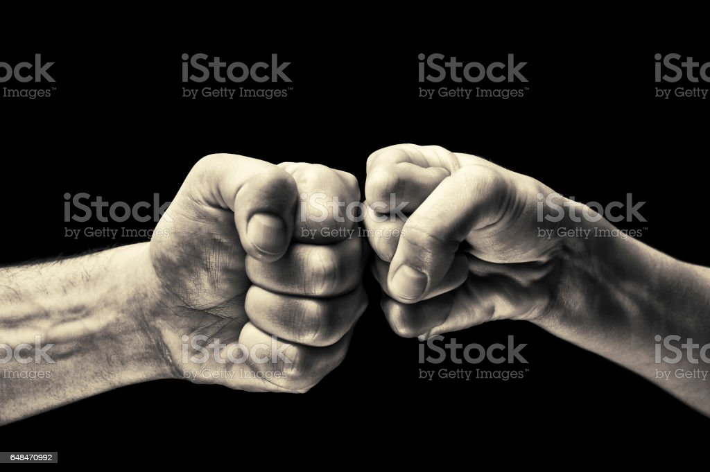 black and white clash of two fists stock photo