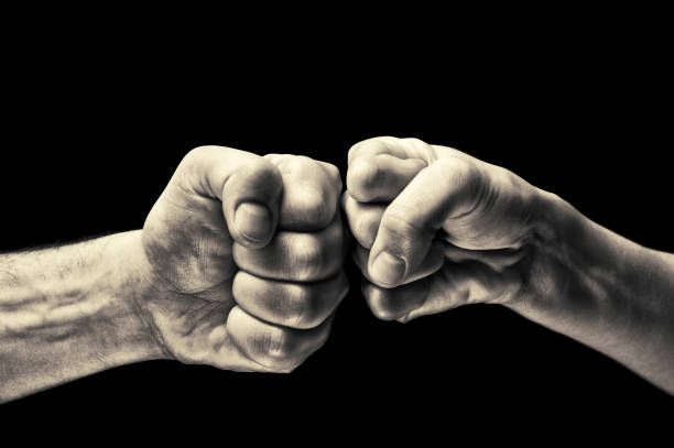 black and white clash of two fists - fist stock photos and pictures