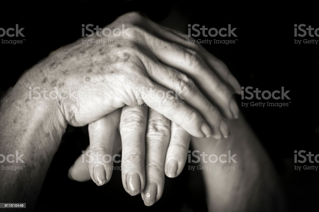 Black and white closeup 75 yers old woman hands on black background,...