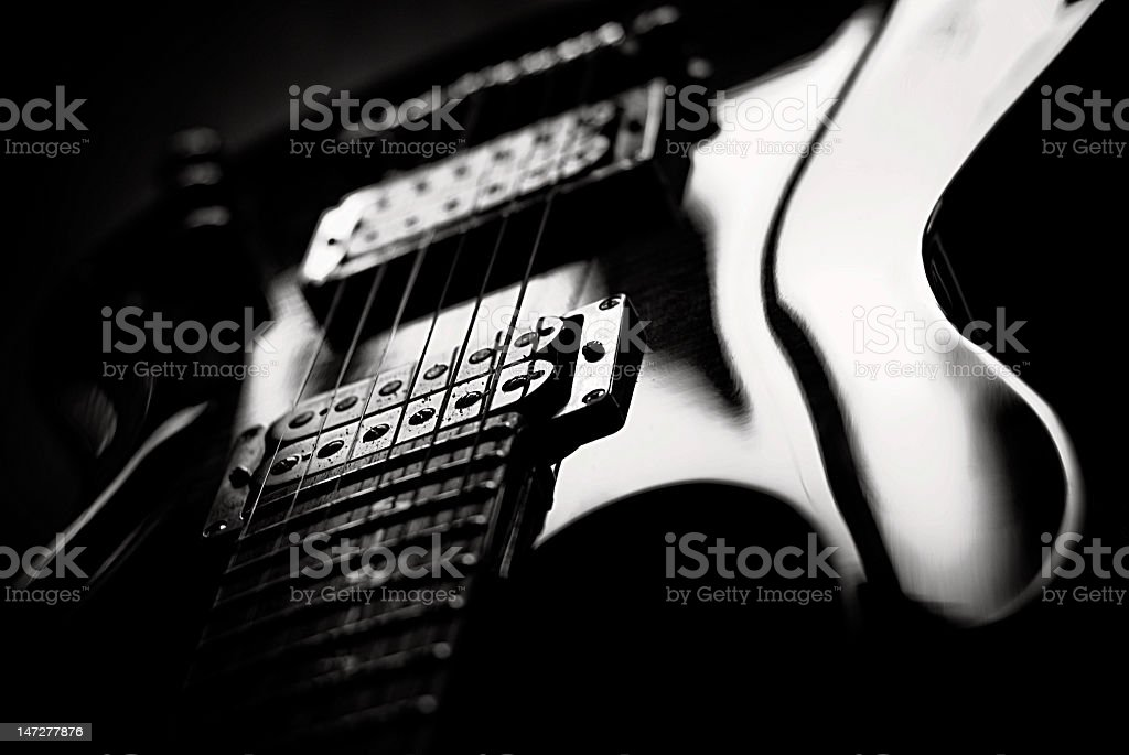 A black and white closeup image of a guitar stock photo