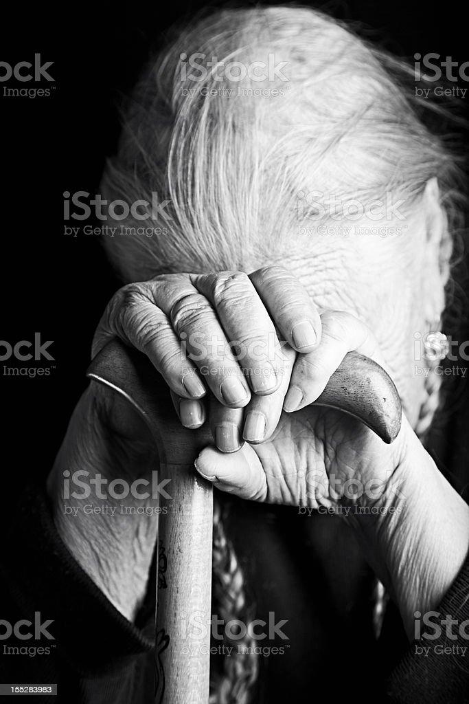 Black and white close-up photo of elderly woman holding cane royalty-free stock photo