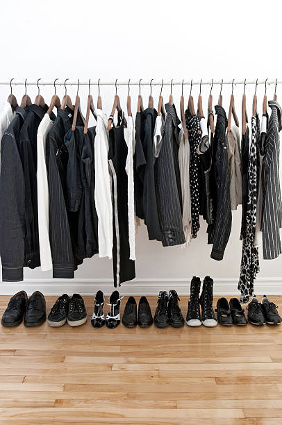 schwarze und weiße kleidung auf bügel - bügelsysteme stock-fotos und bilder