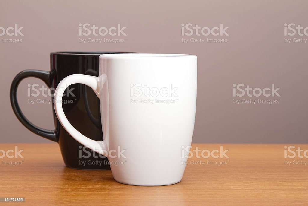 Black and white coffee mugs on wooden table royalty-free stock photo