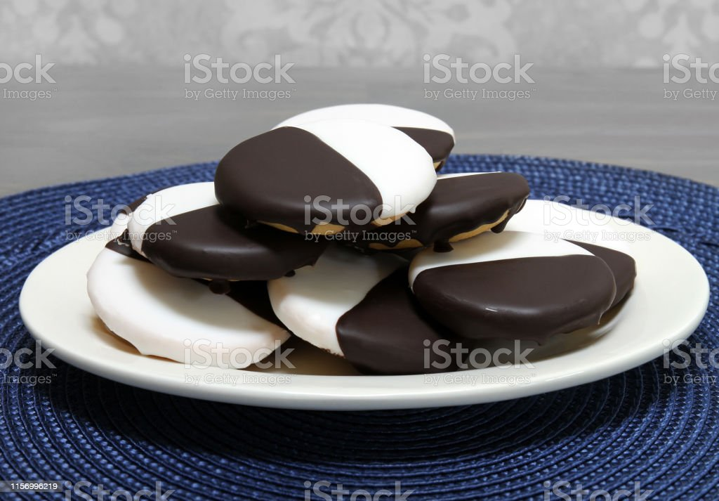 Black and White cookies on an oval plate. Black and white cookies stacked on an oval plate.  Macro, close up with copy space. Baked Stock Photo