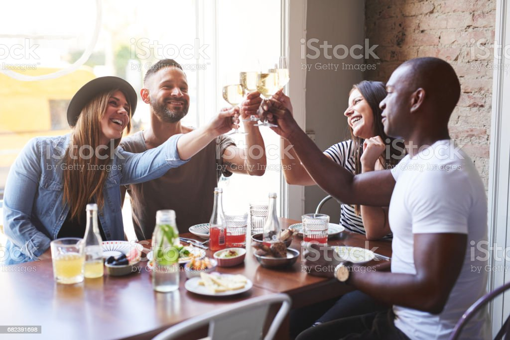 Black and white couples toasting drinks at table royalty-free stock photo