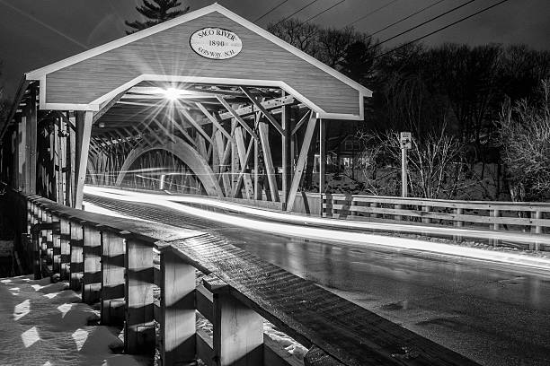 Black and White Covered Bridge Conway New Hampshire Light trails show evidence of a functional wooden covered bridge built in the late 1800's. The fuctional roof protected the roadbed from the harsh winters and intense rains of the White Mountains. conway new hampshire stock pictures, royalty-free photos & images