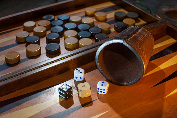 Black and white dices and pieces on a backgammon board stock photo
