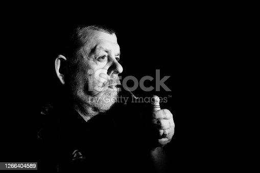 Nice Black and white dramatic portrait of caucasian senior smoking tobacco pipe in darkness