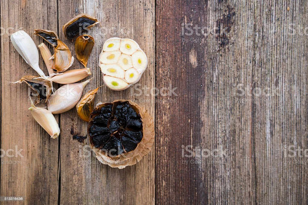 Black and white garlic on wooden background stock photo