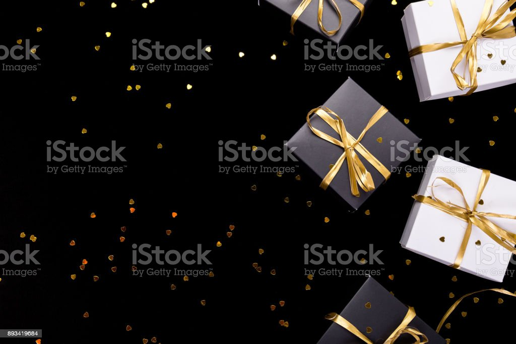 Black and white gift boxes with gold ribbon on shine background. Flat lay. Copy space. stock photo