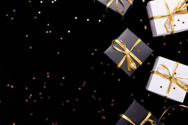 schwarz / weiß-geschenk-boxen mit goldband auf glanz hintergrund. flach zu legen. kopieren sie raum. - teller kaufen stock-fotos und bilder