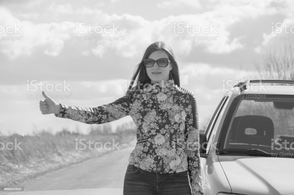 black and white, girl stops the car, holding up a hand stock photo