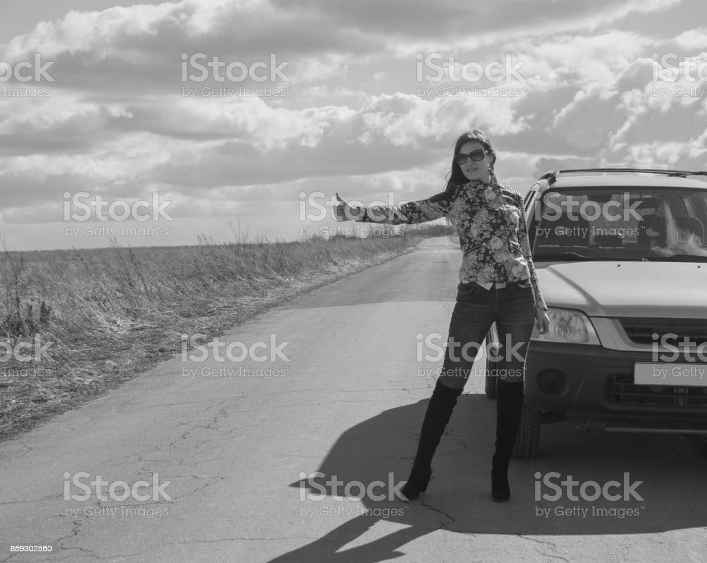 black and white, girl stops the car, raising his hand on a deserted road stock photo