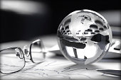 Toned image of glass globe with stock charts, calculator and spectacles.