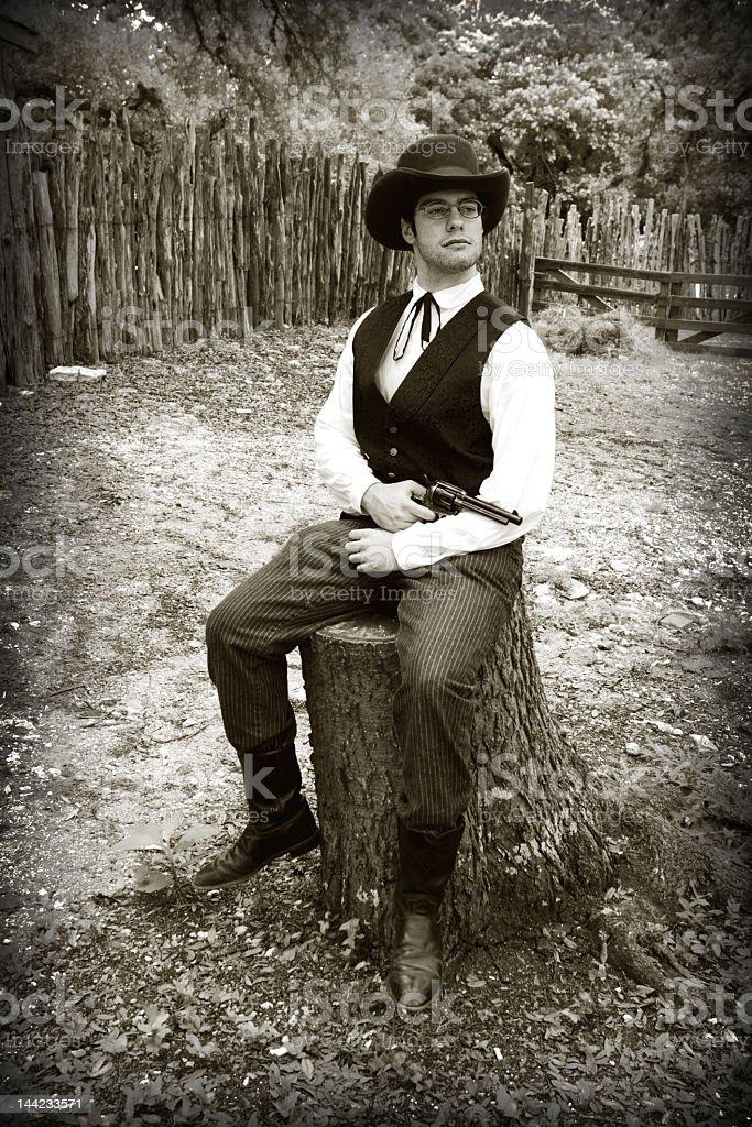 Black and White Gunslinger Cowboy Posing on Stump with Gun royalty-free stock photo