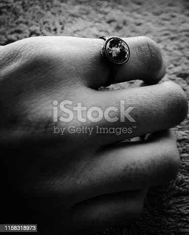 Closeup of hand in black and white with earth ring on her finger