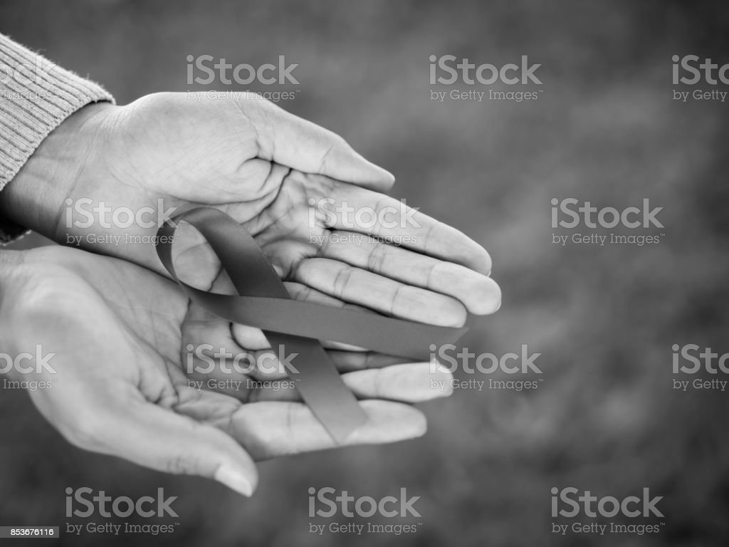 Black and white hands holding red ribbon HIV, world AIDS day...