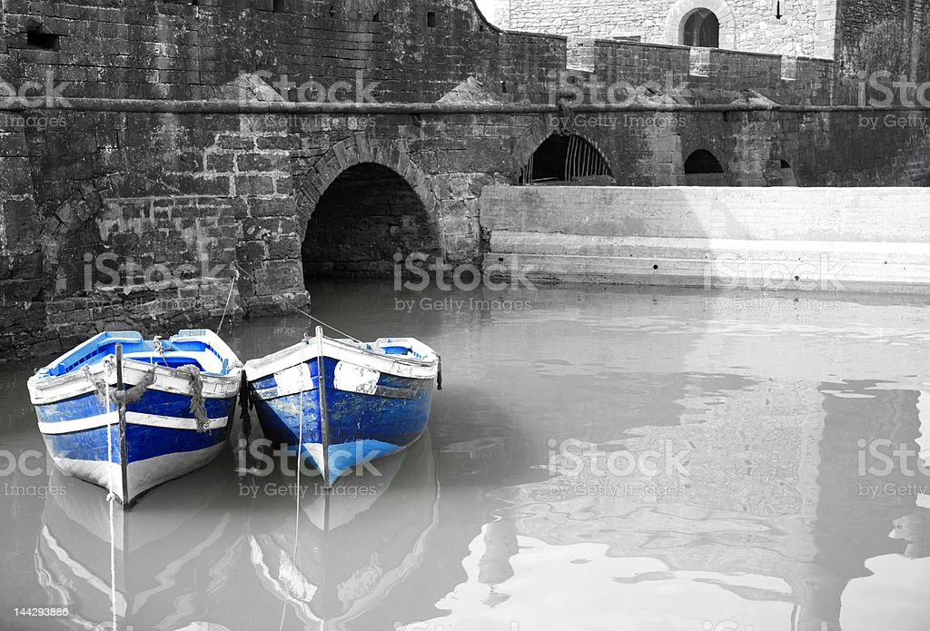 Black and white harbour with two blue boats royalty-free stock photo