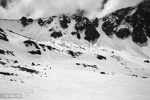 High mountains with snow cornice and avalanche trail, snowy plateau and two small silhouette of hikers at sunny day. Turkey, Kachkar Mountains, highest part of Pontic Mountains. Black and white toned landscape.