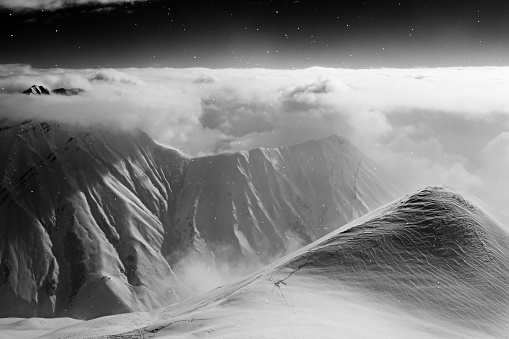 Black and white high snowy mountains covered with beautiful clouds and fog in snowfall. Caucasus Mountains in winter night, Georgia, region Gudauri. Plane view on ski slope for freeride.