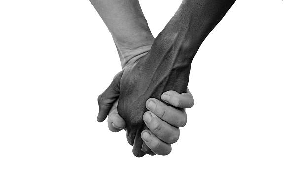 Black and White Hold Hands for Africa Union Peace Love African Peace Symbol. White woman holds hands with a little native African girl, in Bamako, Mali. A black child and a white woman hold hands. Peace on earth symbol. Took this pic during my stay in Bamako, Mali in September 2015. A beautiful shot with lots of possible background symbols. No to Racism! social justice concept stock pictures, royalty-free photos & images