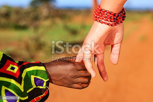istock Black and white holding hands 640255014
