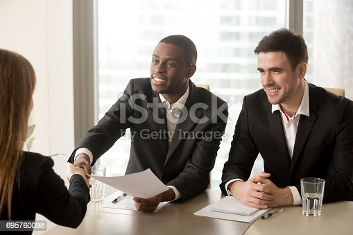 istock Black and white hr recruiters welcoming applicant on job interview 695760098
