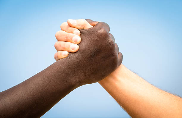 black and white human hands - handshake against racism - welcome march stock photos and pictures