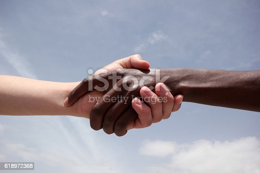istock Black and white human hands 618972368
