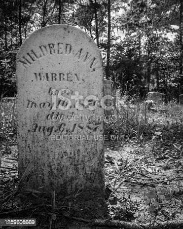 Montgomery County, Alabama/USA-July 20, 2019: Headstone of an eleven-year-old girl in an old wooded graveyard.