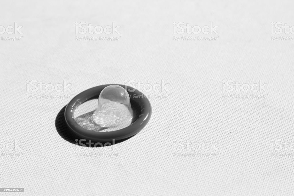 A black and white image of a condom on a canvas board. This image can be used to represent contraception. stock photo