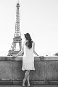 Parisian Girl Defocused In Front Of The Sharply Focused Eiffel Tower As She Looks To Her Right Side In Monochrome.