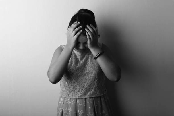 imagen en blanco y negro de una chica deprimida colocando sus manos sobre la cabeza - vergüenza fotografías e imágenes de stock