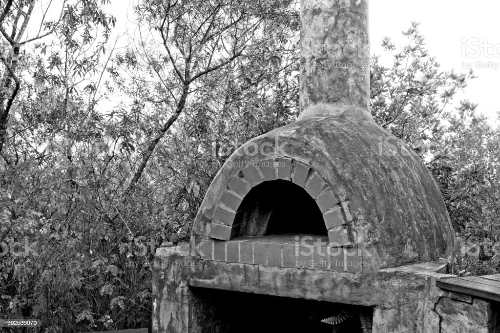 A black and white image of a outside wood fired pizza oven which was constructed with cement and bricks. - Royalty-free Black Color Stock Photo
