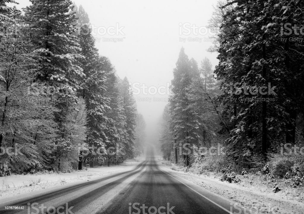 Black and white image of a road through a snowy landscape, fading into the horizon stock photo