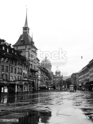 Bern / Switzerland - FEB 2, 2020: Black and white image of a medieval old town, Bern with Käfigturm (a 17th-century Baroque tower with a clock and bell), Bundesplatz, and The Parliament Building (Bundeshaus) in the background.