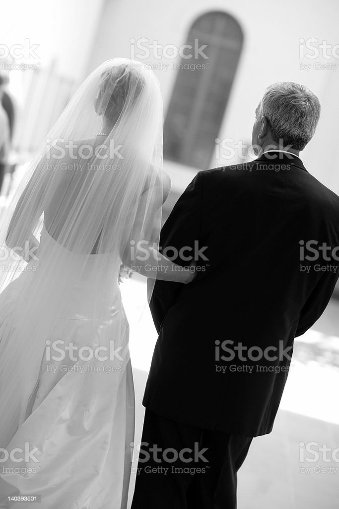 Black and white image of bride and father from behind stock photo