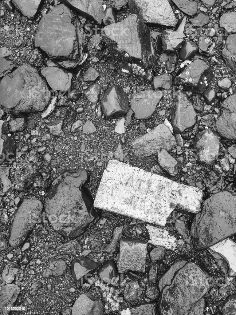 Black and white image of broken bricks and stone on the beach stock photo