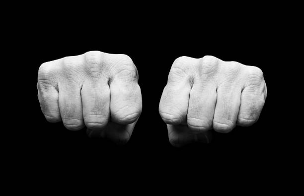 black and white image of clenched fists - knuckle stock photos and pictures