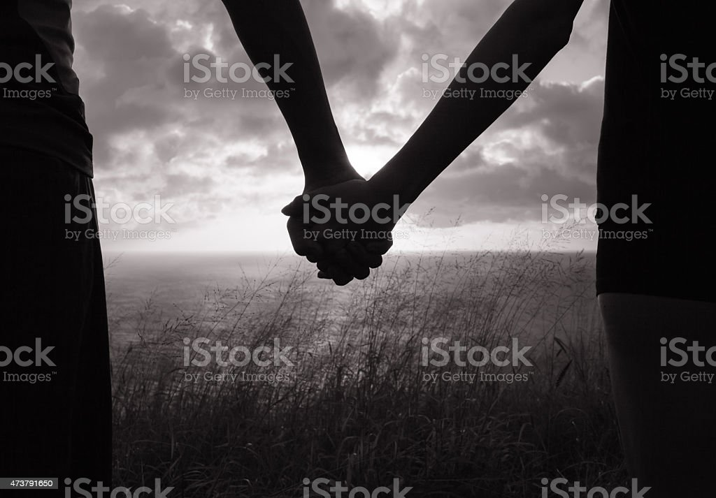 Black and white image of couple holding hands in silhouette stock photo