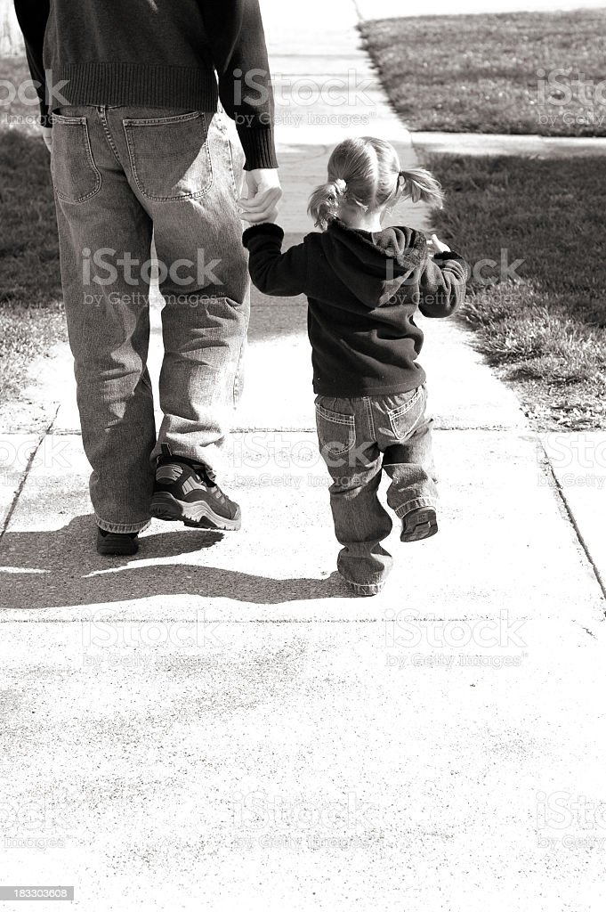 Black and White Image of Little Girl Wallking With Daddy royalty-free stock photo