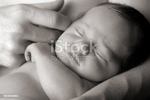 Black and white image of newborn baby being lovingly held by father.  Closeup headshot.