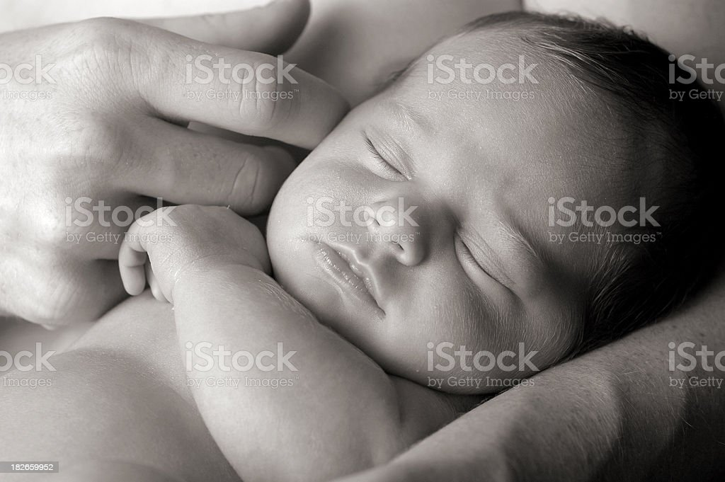 Black and White Image of Newborn in Father's Loving Arms stock photo