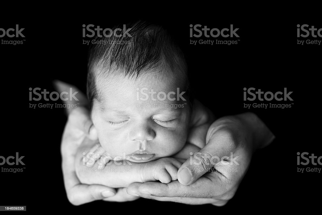 Black and White Image of Newborn Sleeping in Father's Hands stock photo