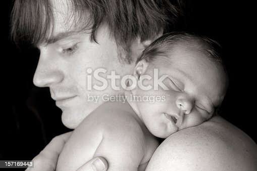 Close up black and white image of a precious newborn baby sleeping on father's shoulder.  Isolated on black.